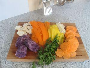 Das zu frittierende Gemüse im Uhrzeigersinn: vorne links die violetten Erdäpfeln, dann der Sellerie, rote Karotten, gelbe Karotten, Petersilienwurzel, Süßkartoffel und Petersilie.