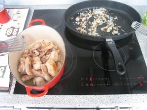Die angebräunten Kaninchenstücke sind im Schmortopf gelandet. In der Pfanne werden die weiße Zwiebel mit den Rosinen angeschwitzt.