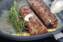 Lammrücken mit Butter und Aromen verfeinern.